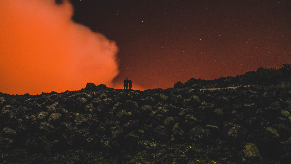 Two tourists staring down into the lava lake of Mount Nyiragongo.