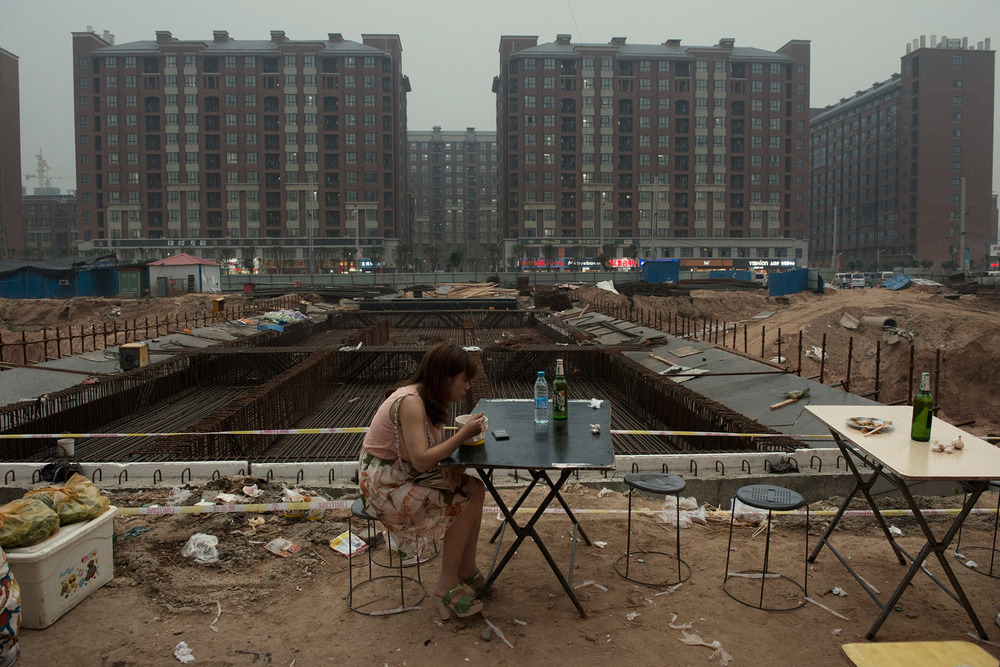 A lone diner at an outdoor restaurant next to a construction site at the Foxconn factory town on the outskirts of Zhengzhou.