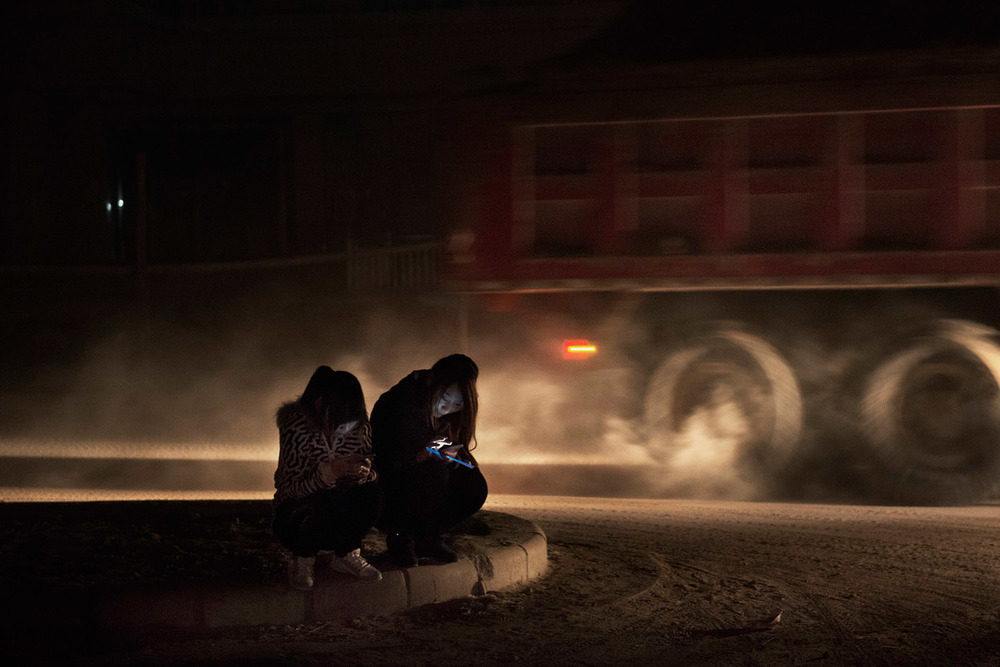 On a dirt road of Foxconn factory town on the outskirts of Zhengzhou, two girls checking their smartphones while a construction truck is passing nearby.