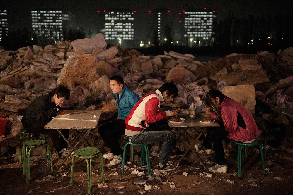 Foxconn workers having dinner in a small outdoor restaurant in front of their dorms.