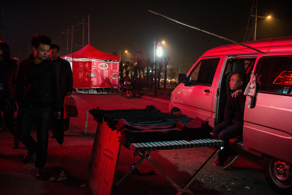 Foxconn workers passing by a cloth vendor. The sudden influx of young workers in what was a rural suburb of Zhengzhou has attracted many small businesses ran by locals and catering to the workers needs.
