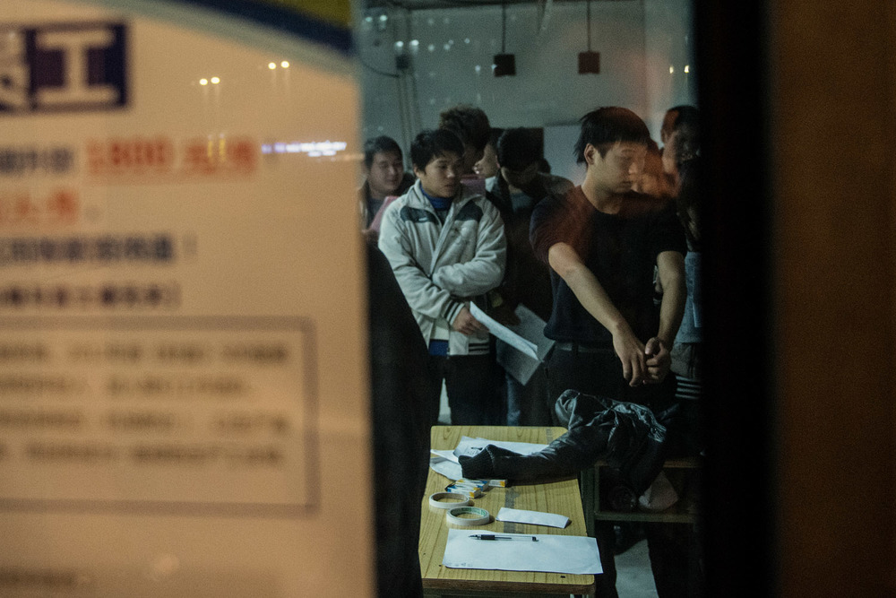 It's past 10 pm at Zhengzhou's Apple city and recruiters are still busy. A young man is showing his forearms at recruiters. Any sign of a tattoo would be disqualifying. However, when in shortage of workforce Foxconn recruiters overlook this precondition.