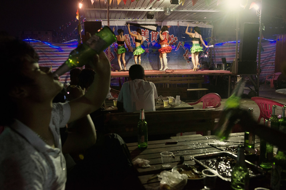 Foxconn workers drinking beer during a transvestites show at an outdoor restaurant in the Foxconn factory town.