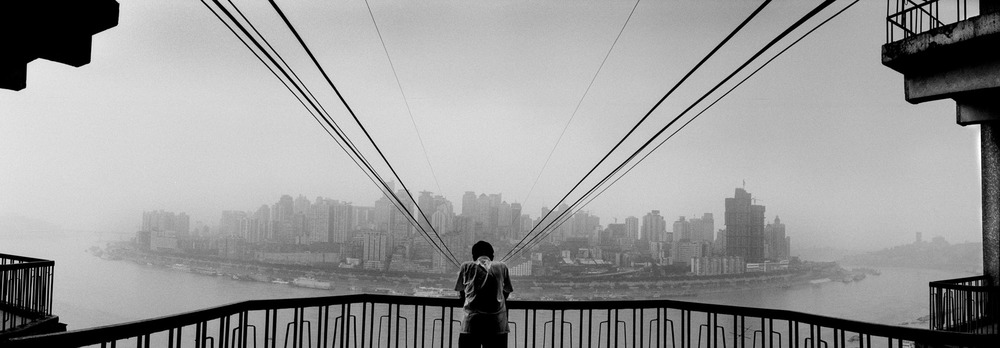 A man staring at Chongqing skyline from the cable car station. Chongqing is the upstream gate to te reservoir created by the three gorges dam. It is also one of the fastest growing city in China. In spite of its growth it is crippled by unempolyment due to the influx of population who had to leave the three gorges area.