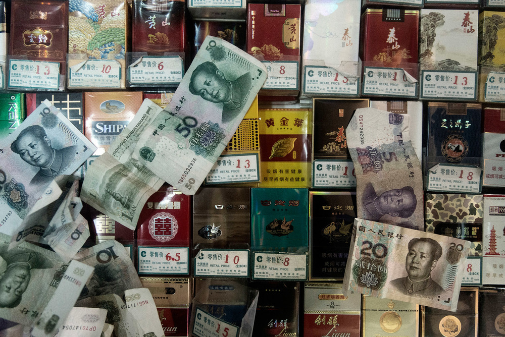 Bank notes on packs of cigarettes at a retailer in Beijing.  The tobacco industry in China is state-owned and contributes annually to close to 10% of the central government revenues.