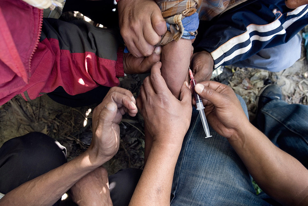 Drug addicts helping each others to inject Norphin, an addictive pain killer cheaper than heroin. They are struggling to fight a blood vessel.