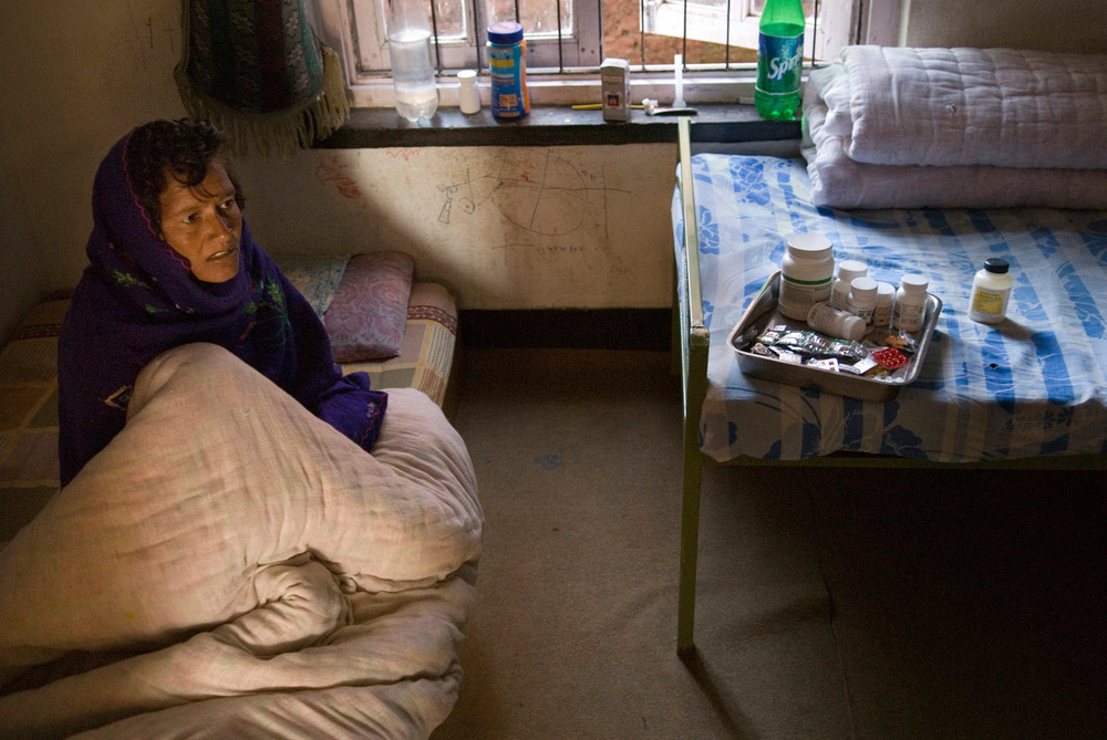Joti (30 years old) in her bed during the distribution of antiretroviral drugs. She suffers from various HIV related infections and walk with difficulties. She got contaminated with HIV by her husband a migrant worker.