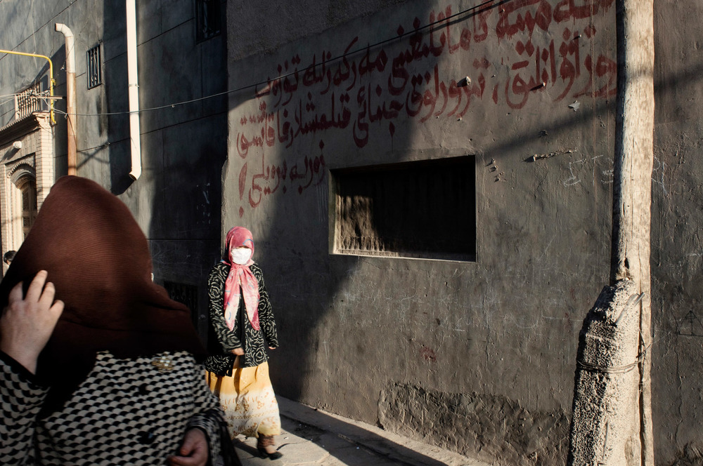 "On a street of Kashgar, two veiled women passing a wall with some writing in Uighur : ""let's centrally correct the safety of society, and deal a hard blow against violence, terrorism, and criminal acts!"". Xinjiang Southern crescent and the region of Kashgar is the most unstable of the whole province with many eruptions of violence resulting in numerous death. Those events are consistently labelled as terrorist acts by the authorities."