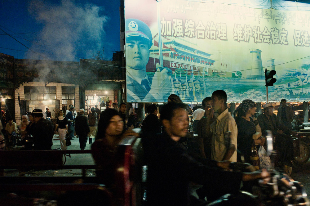 At a night market in Kuqa, Uyghurs passing by a propaganda poster featuring People's Liberation Army.