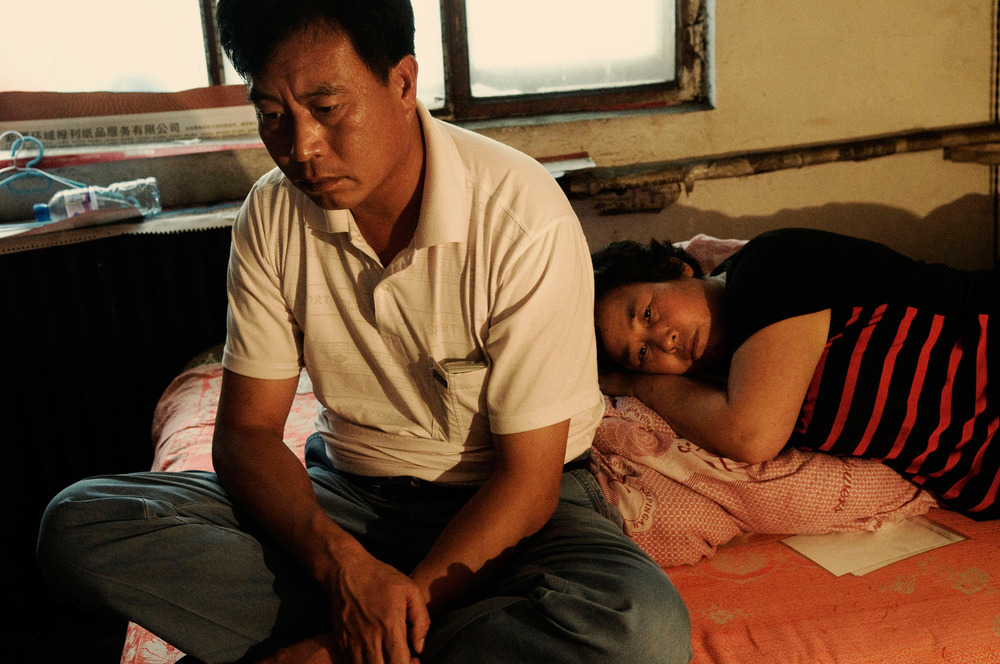 Zhang Aiying lying on her bed next to her husband, Lu Sifeng, in their room. They have lost their son, 25 years old Lu Huakua, hacked to death by a Uyghur mob, during the July 5th riots in Urumqi. The couple originally from Henan had moved to Xinjiang a couple of years before, in search of work opportunities. They were selling fruit and vegetables in a mixed neighbourhood of Urumqi.