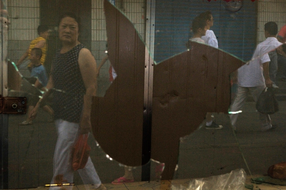 In Urumqi, passers-by reflect on the shattered window of a small store vandalized during the 2009 riots which resulted in the death of over 200 Han people. The riots have been a turning point for Xinjiang, leading to heavy handed repression by Beijing and deepening the chasm between Uyghur and Han population.