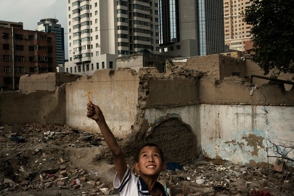 A kid playing in the ruins of traditional houses in a Uyghur neighbourhood of Urumqi.