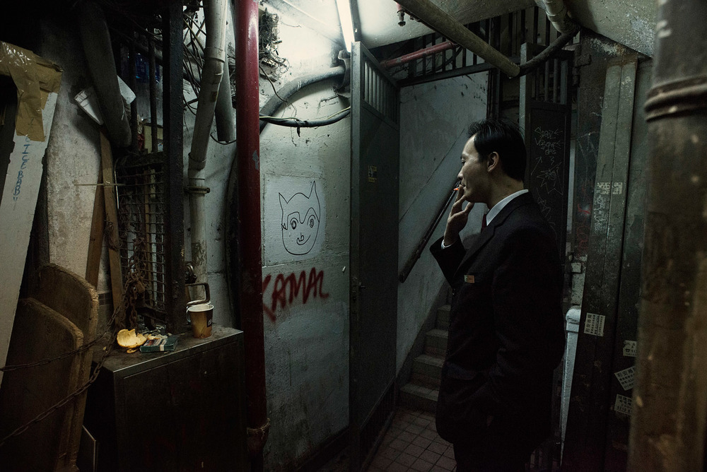 In a back alley of the Chungking Mansions, the staff of department store is taking a cigarette break.