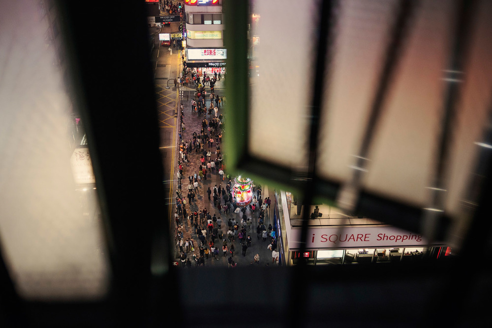 A view on a busy street of Hong Kong through the bedroom window of a Chungking Mansions guest house.