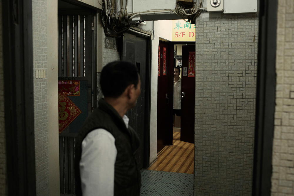 On the 5th floor of a Chungking Mansions tower, a resident is cautiously opening his apartment door.