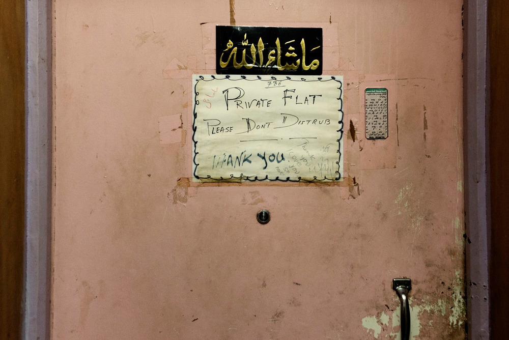 Inside the Chungking Mansions, the door of a private apartment. Most of the residents of the Mansions are transient workers and hostels guests. However a few families live there in spite of the building bad reputation.