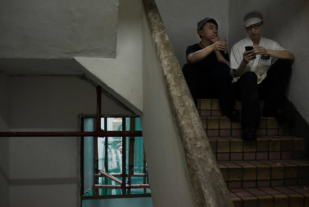 In a staircase of the Chungking Mansions, two cooks from a nearby fast food restaurant are taking a cigarette break..