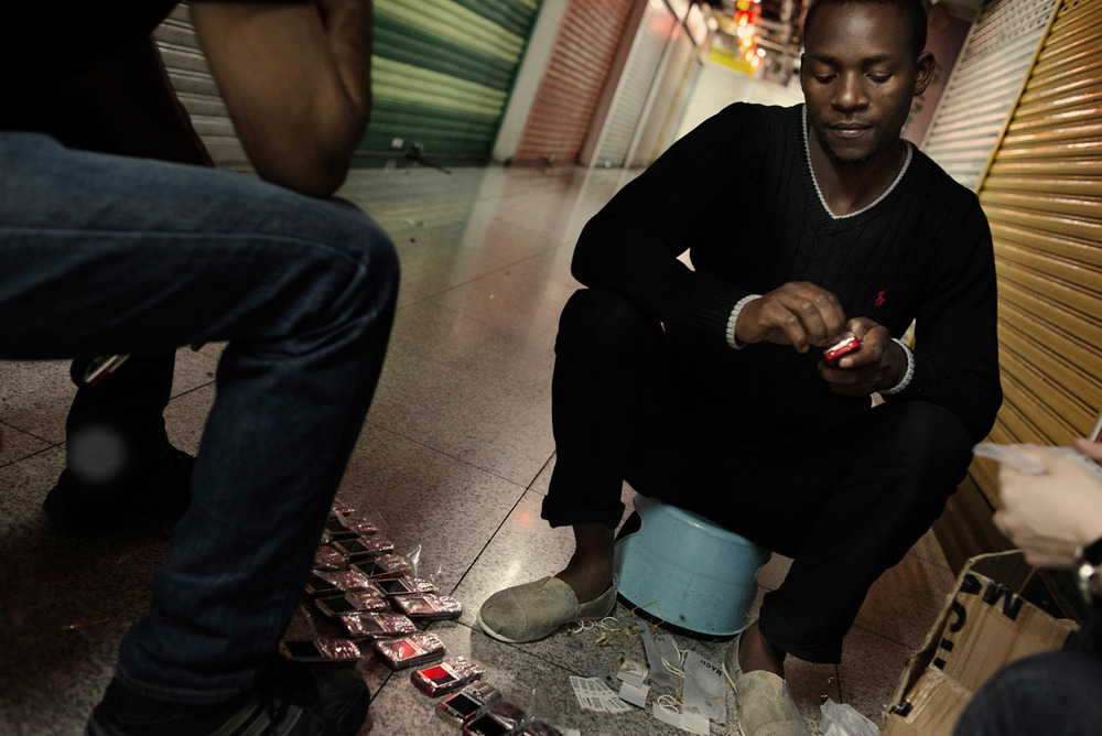 In a commercial alley of the Chungking Mansions an African trader is checking one by one a batch of mobile phones he bought and plans to ship to Africa.