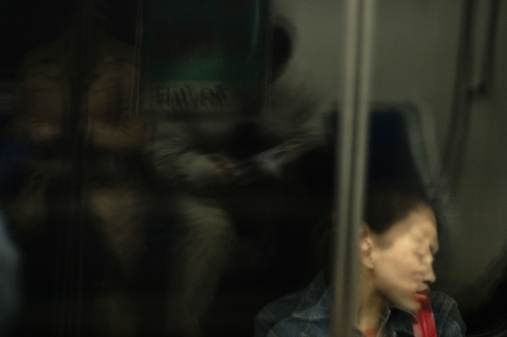 Half awake, half asleep, lost in self reflection or somewhere else, oblivious of our fellow commuters, we travel. The subway takes us to another world. It's in Beijing subway but could be in any other subway in the world.