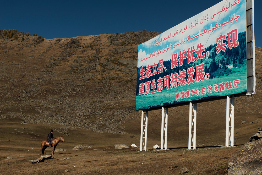 "A Kazakh nomad on his horse, in the grasslands of the Altai range, facing a propaganda billboard saying : ""The foundation of this county is in its environment; environmental protection is the priority; must realise sustainable development of the grassland"".  In this region, many nomads have left for neighbouring Kazakhstan, rather than be forced into sedentary farming for which they have little knowledge."