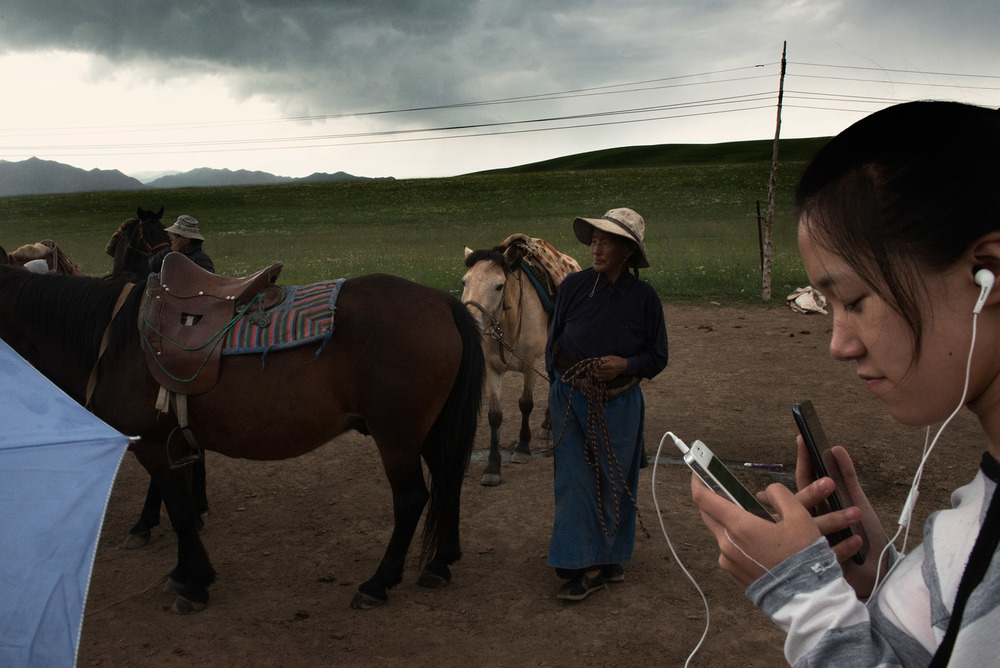 A Chinese tourists at a horse-riding camp set-up by Tibetan nomads in the grassland near Xiahe (Gansu). Some nomads in the region have set-up camps for tourists, cashing on the fascination for nomadic lifestyle. A new source of income for them as their livelihood is under threat by a resettlement plan.