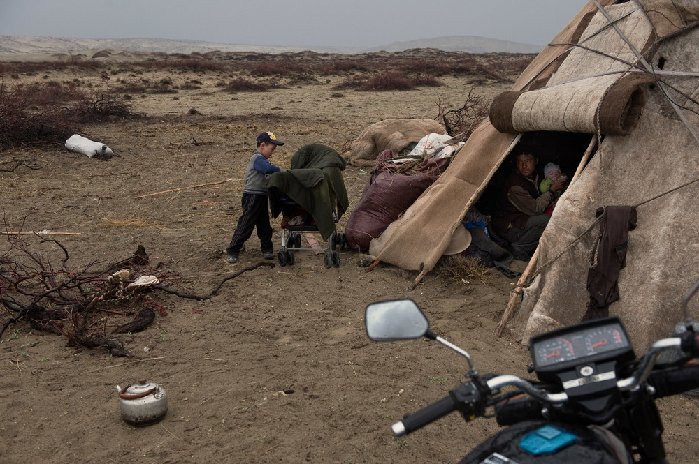 In his tent, a Kazakh nomad feeding his 9 months old daughter with a bottle, while his son is playing outside the family tent. They are on their way to the summer grassland and have establish camp in a deserted landscape. Desertification has been intensifying and is an environmental threat in the region. The government claims overgrazing is responsible for it, and has developed a policy of forced settlements for nomads, threatening the livelihood of the local Kazakh nomads. Hundreds have moved to nearby Kazakhstan as  result. This nomad owns a dozen camels, 25 cows and a hundred sheep. The family earns between RMB 10 000 and 25 000 a year. He also plans to follow the example of some of his relatives and leave China for Kazakhstan.