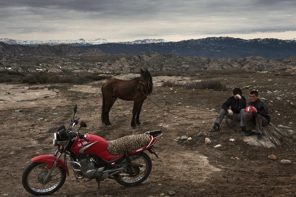 Meilan (left) and his cousin, two ethnic Kazakh herders, take a break in the barren landscape of Northern Xinjiang. Meilan would like to quit the nomadic life and find work in the city but can not, he is the elder son and has to take care of the family livestock. The nomads resettlement policy may meet the aspirations of some nomads, especially younger ones who dream of another life, however most herders have no alternative source of income.