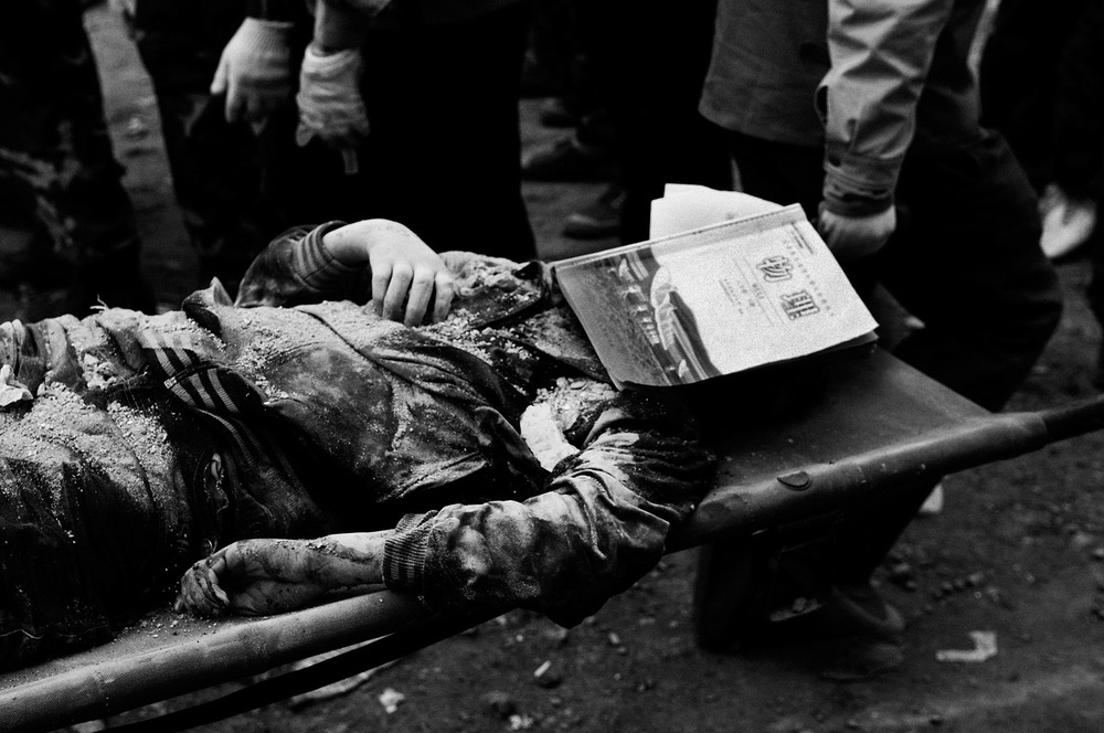 The dead body of a student at Beichuan middle school is being carried away,his face covered with a physics text book.