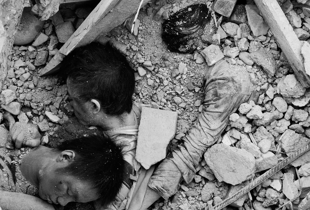 The dead bodies of 3 students at Beichuan high school. They died together. 1400 students from that school perished that day. The official toll is 800.  The poor building quality of schools buildings in the earthquake region explain the high number of children victims and has been a subject of controversy. Many critics faulting government corruption for it have been harassed and jailed.