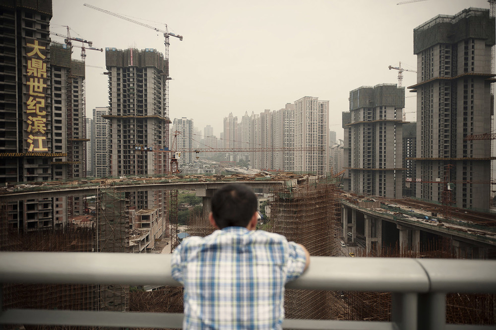 """A man staring at a large residential complex under construction by the Yangtze in Chongqing. Part of the """"Chongqing Model"""" developed by Party Secretary Bo Xilai includes the construction of social housing. Chongqing has the fastest growing GDP in China. R esidential housing investment as a share of China's GDP has tripled from 2% in 2000 to 6% in 2011."""