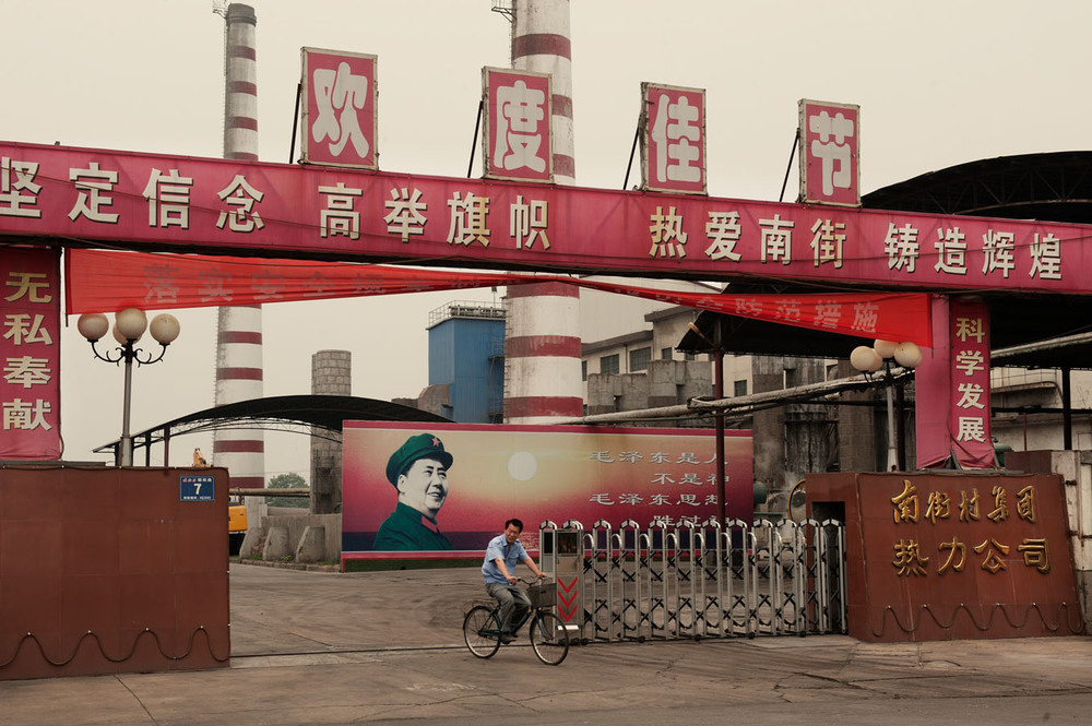 "A worker leaving Nanjie heating factory on his bike. Above him a propaganda banner says: ""Forge one's determination, hold the flag high, love nanjie and build a place of glory"". Behind him, inside the factory a billboard featuring Mao with the writing""Mao Zedong is a human being, not a God. But Mao Zedong thought is greater than God""."