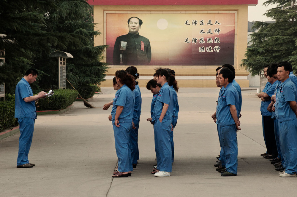 "Workers standing up for the call before taking their shift at a factory in Nanjie. Behind them stands a large billboard with Chairman Mao and the slogan """"Mao Zedong is human being not a God, but Mao Zedong thought is greater than God""."