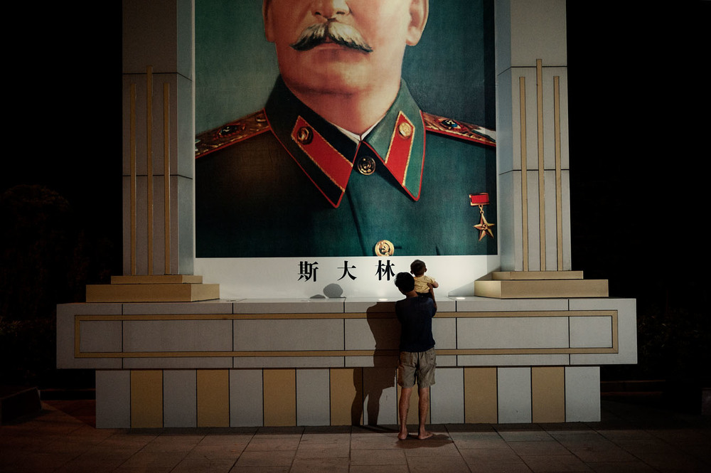 Father and son by a giant portrait of Stalin on the East is Red square of Nanjie (Henan)