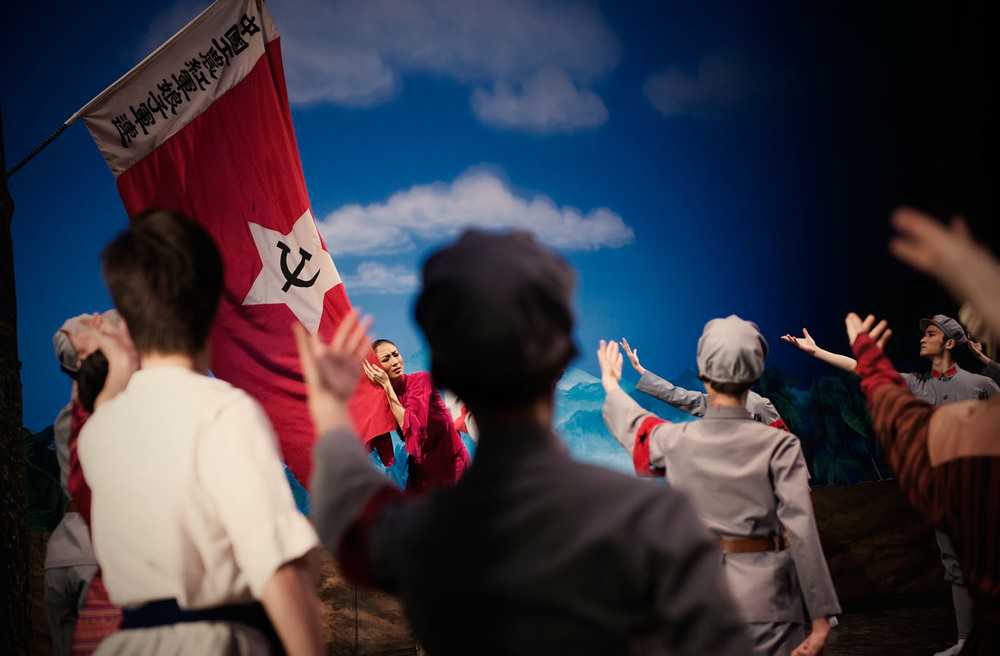 "A dancer embracing the Communist Party flag during a representation of the ""Red Detachment of Women"", one of the eight model operas which dominated the National stage during the Cultural Revolution.  The ballet remains one of the most popular in China and is still regularly staged throughout the country."