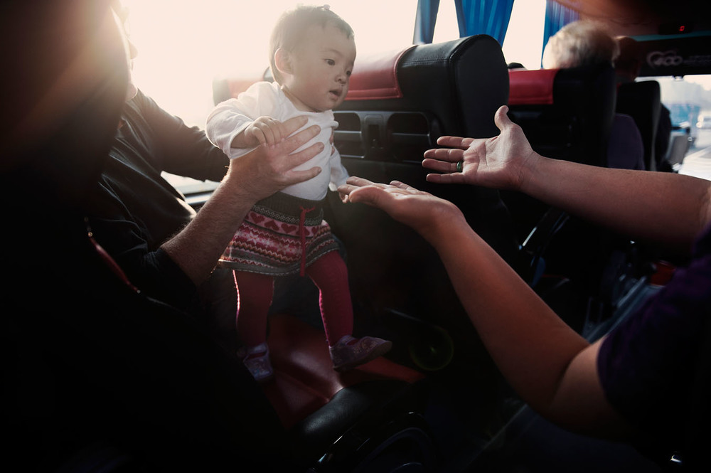 On the bus taking them back to the White Swan Hotel from the U.S. Consulate, Peggy is taking in her arms Bridget her newly adopted daughter. Peggy decided to adopt rather than go for a risky pregnancy at 45 years old.