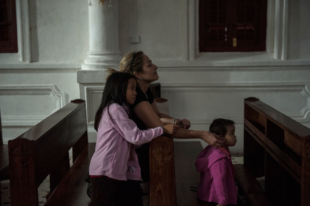 Carmen, the spanish mother of two adopted girls has come to pray in the French catholic church of Shamian island. Many of the adopting parents are Christians and religion plays a part for many of them in the decision to adopt.
