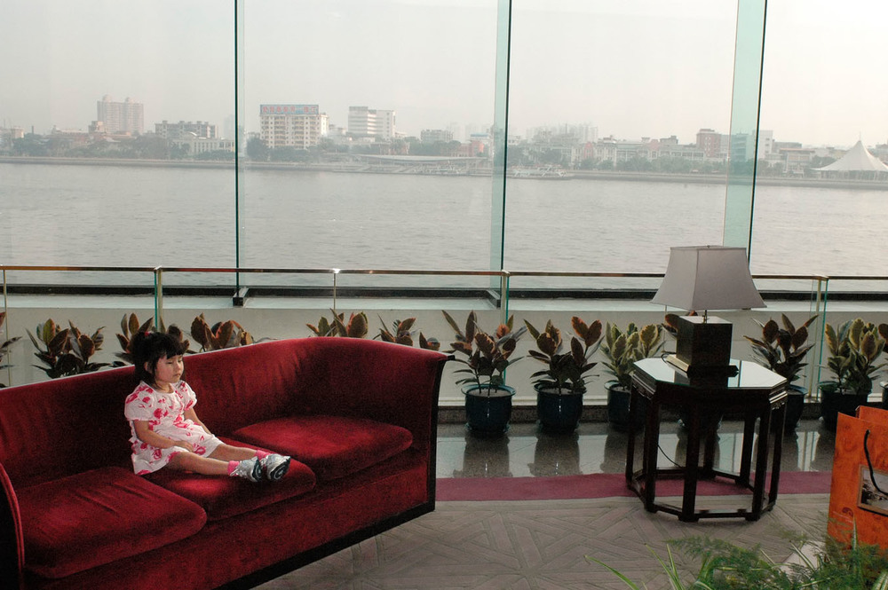On the island of Shamian in Guangzhou, a 5 years old American girl adopted a few years ago in China has come back to Guangzhou as her parents are adopting another baby. She is quietly sitting on the couch of the White Swan Hotel as their parents are having their picture taken with her new sibling.    The island of Shamian where numbers of foreign consulates have historically been  located, is a hub for adopting parents in China. They spend their first days with their adopted child on the island, going through the last administrative steps before heading back to their home country. They usually stay at the White Swan Hotel.