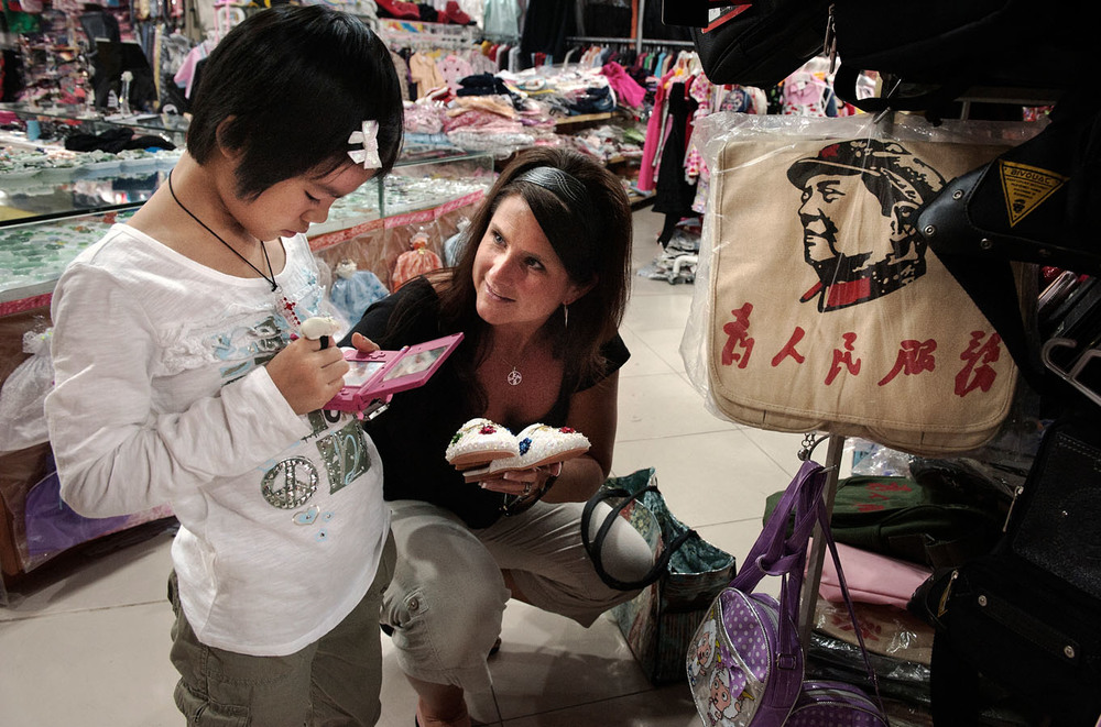 In a tourist store of Shamian Island, Terri is showing a pair of sleepers to 9 years old Maylinn. Maylinn busy with her video game and with no knowledge of English, doesn't answer. Maylinn has just been adopted by Chad and Terri, she is their second adopted and third child. Children are rarely adopted at such a late age, the integration in the adoptive family, and country, and the language problem make the process difficult.
