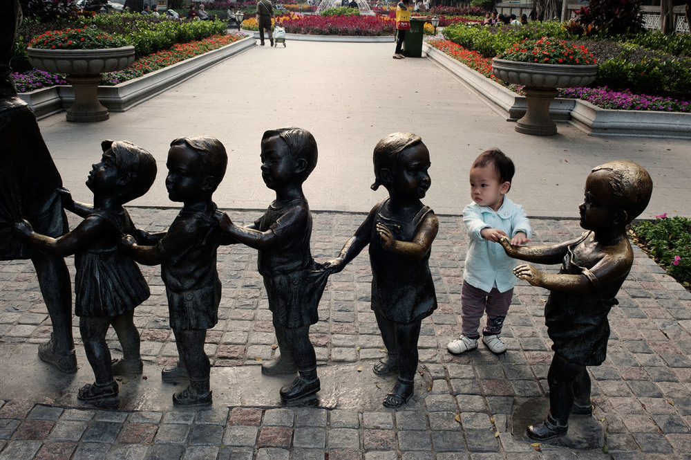 On Shamian Island in Guangzhou, an adopted child near a sculpture representing school children.