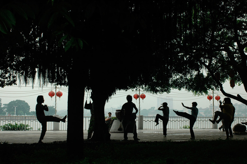 On the banks of the Pearl River on the islands of Shamian, locals are practicing Tai-Chi.