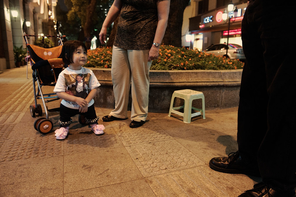 "On a street of Shamian island, 7 years old Emmalee with her adoptive parents Marvin and April. Emmallee is suffering from Phocomelia a genetic disease causing legs atrophy. Emmalee is the 6th child adopted by Marvin and April. All suffering from disabilities. They also have three biologic children. Emmallee's adoption cost them $24,000. They didn't visit Emmallee's orphanage which would have cost them an extra $300. ""Everything is about money"" says April."