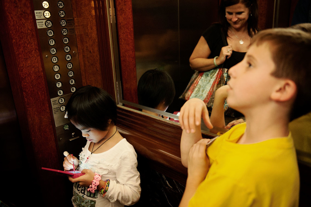 In an elevator of the White Swan Hotel, Dylan (right) with his newly adopted sister Maylinn, and their mother Terri.