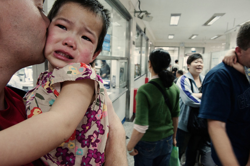 At Shamian island medical centre, 2 years old Tate crying in the arms of her adopted father, Nate. Tate traumatised by the anti-tuberculosis vaccine she got the day before, has come back for a health check. Nate with his wife Tommy are from Minnesota and Tate is their third child and their first adopted one.