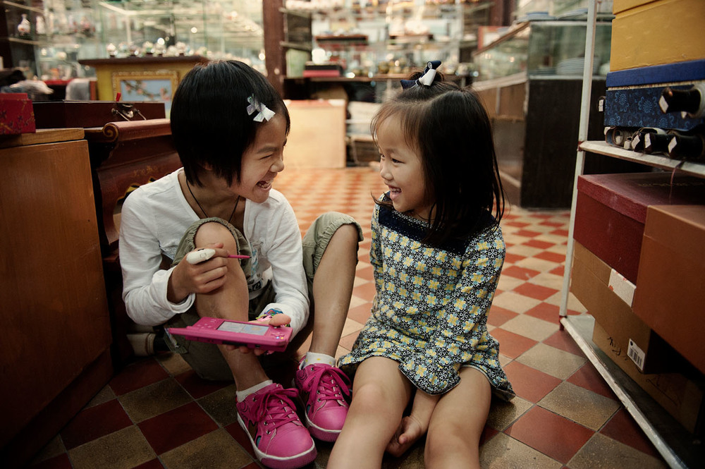 5 years old Anna Lei (right) Anna lei with 9 years old Maylinn (left) playing together in a tourist shop of Shamian island. A week before they didn' know each others. They are now sisters as both of them have been adopted by Chad and Terri from Indiana. Annalei the youngest one, was adopted 4 years before and made the trip to China with her parents to get Maylinn who doesn't speak English yet.