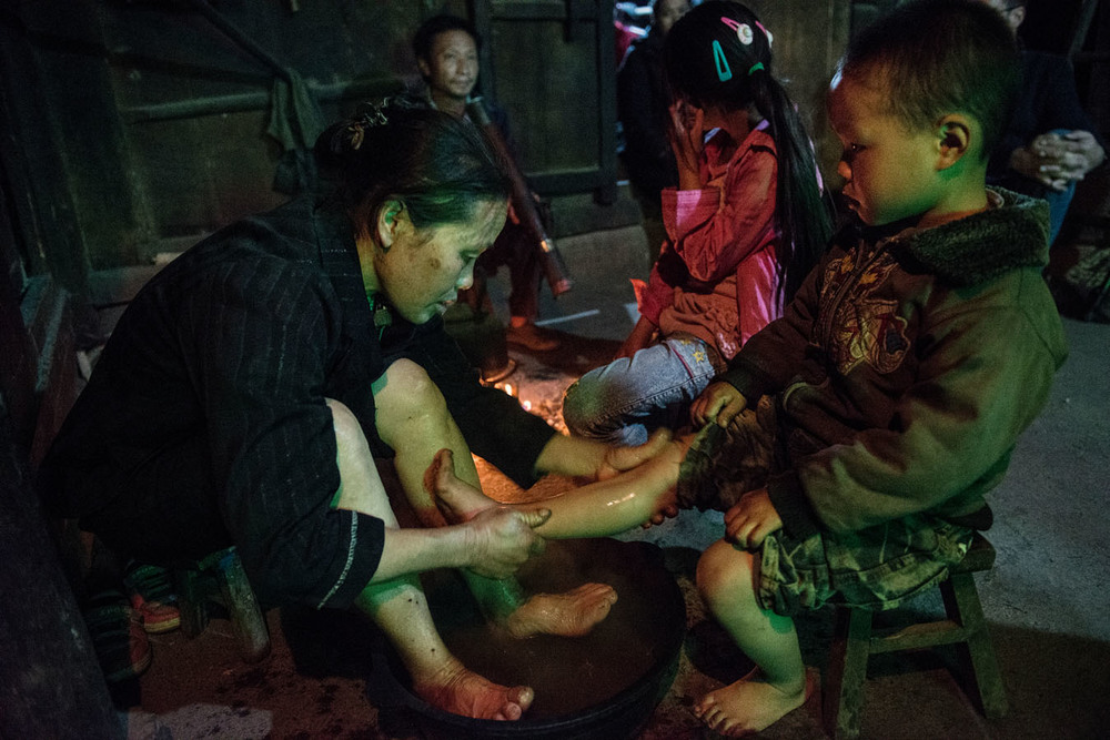 Tian Mei's 3 years old little brother is having his feet washed by his grand mother from a water basin, a nightly ritual in the yan family. The house has no running water and it has to be brought from the pond. The Yan grand parents have to take care of their for grand children.