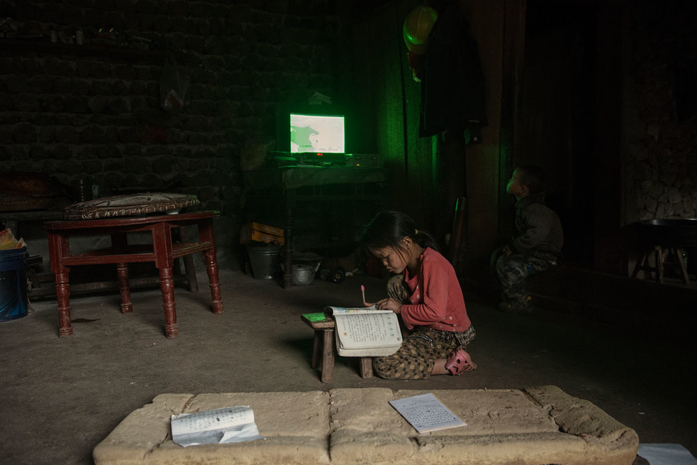 8 years old Ting Fe doing her schoolwork, while her little brother is watching tv.