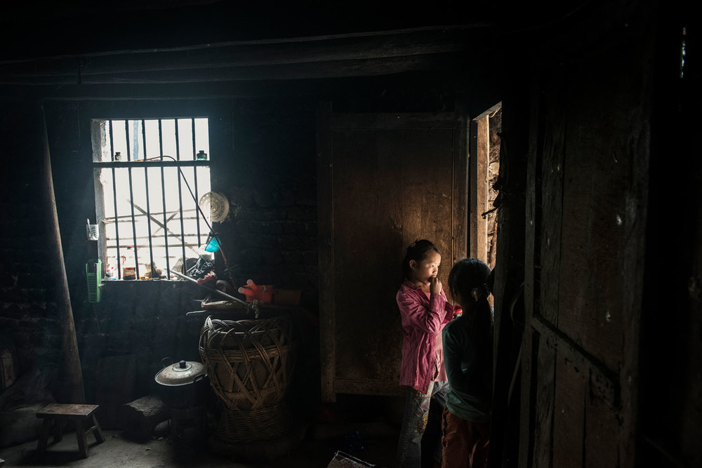 11 years old Yang Tian Mei, standing by the door of the kitchen with one of her sisters, at her grand parents' home.