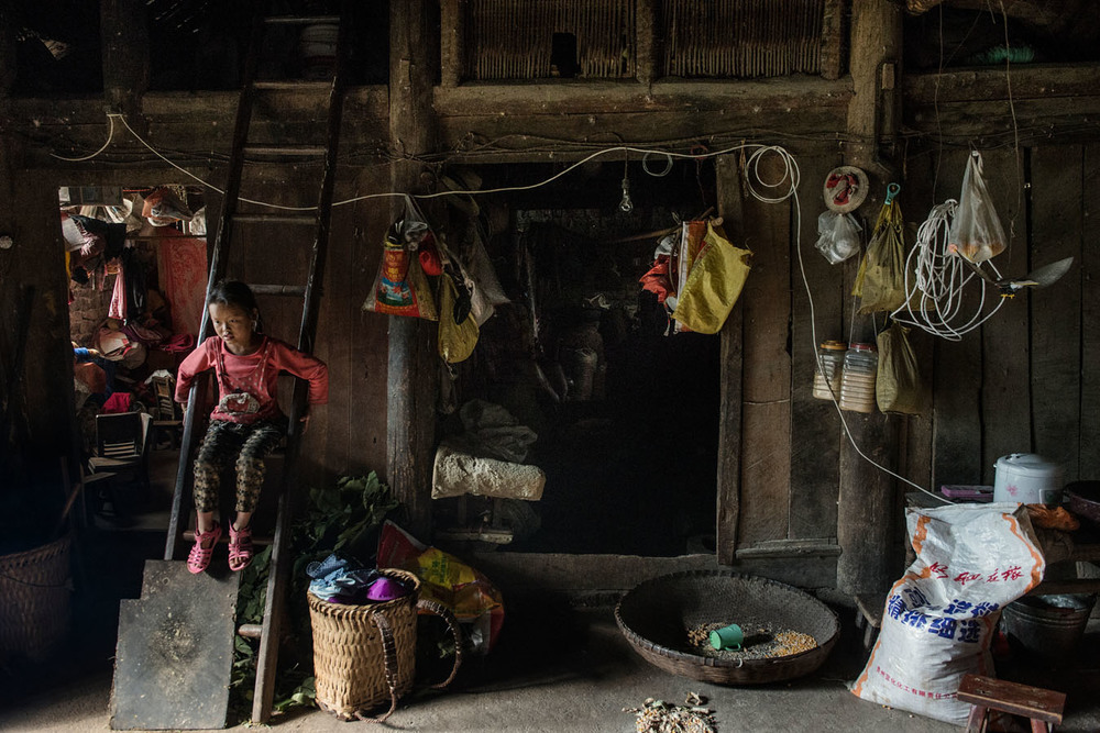 8 years old Ting Fen, Ting Rui's older sister, standing on a wood ladder in the main room of her grand parents's home, on a day she and her siblings were left alone at home. Ting Fen's father works hundreds of miles away, while her mum has disappeared.