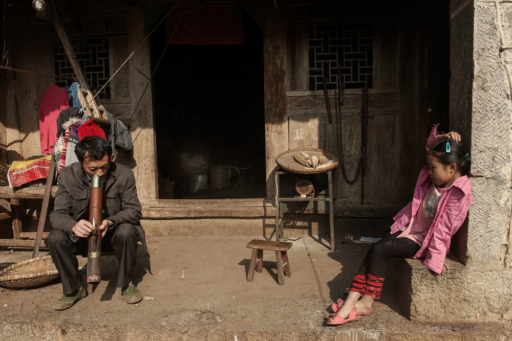 11 years old Yang Tian Mei, standing with her grand father under the porch of the family home. Her grand-father has just come back for a lunch break from working on the construction side of a dirt road which will link the village with the local asphalt road. Before lunch he is smoking tobacco through a water pipe.