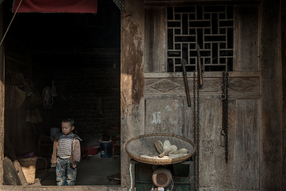 4 years old Ting Rui, Hailian cousin, standing at the door of his grand parents home on a day he and his sisters were left alone at home. Ting Rui's father works hundreds of miles away, while is mum has disappeared.